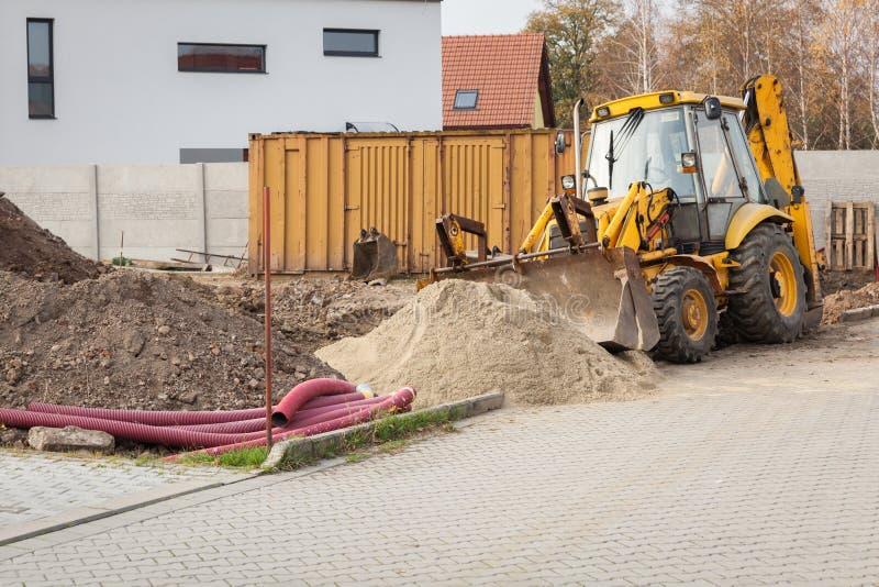 L'excavation de terre fonctionne à côté de l'excavatrice à la construction d'une maison photo libre de droits