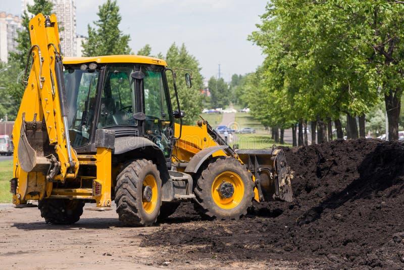 L'excavatrice étend la terre fraîche sur la pelouse photographie stock