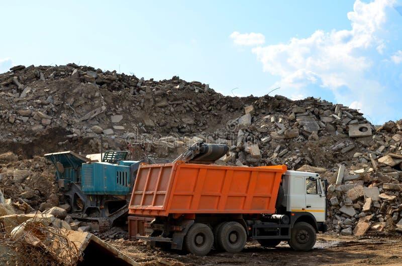 L'excavatrice charge des déchets de construction dans le défibreur mobile concret renforcé pour écraser, réutilisation des déchet image libre de droits