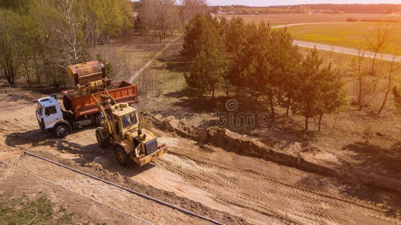 L'excavatrice charge le sable dans le camion Les travailleurs font la mani?re photos libres de droits