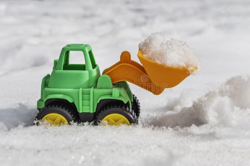 L'excavatrice en plastique verte de souvenir de jouet avec la pelle orange à seau et les roues jaunes dégage la neige sur un fond images stock