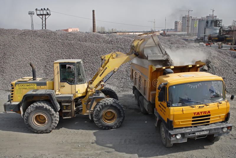 L'excavatrice jaune charge le gravier dans le verseur orange de camion de déchargeur images libres de droits