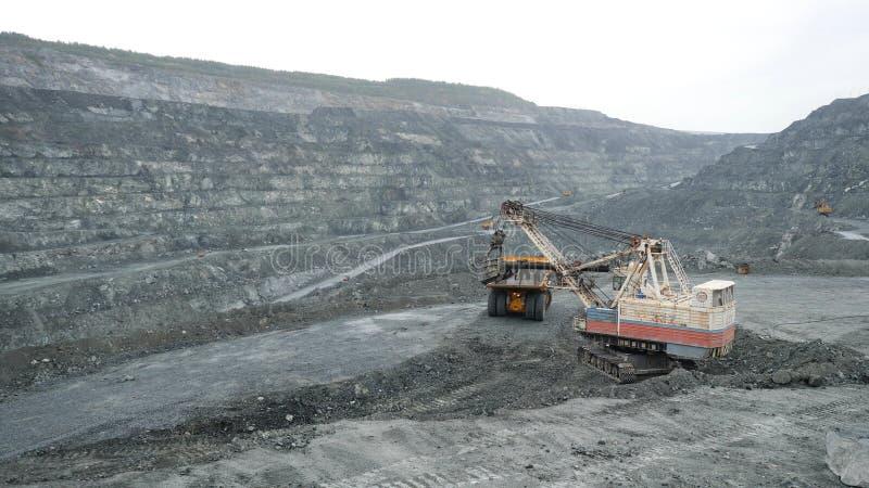 L'excavatrice remplit camion à benne basculante de terre dans l'exploitation à ciel ouvert Travaux de machines lourdes dans l'ind photos stock