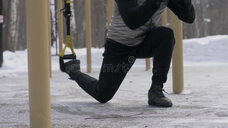 L'exercice et le saut de posture accroupie de formation d'homme s'exercent avec l'extenseur de forme physique extérieur image libre de droits