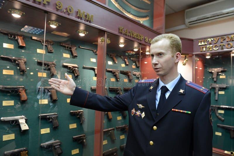 L'expert légal de police démontre des échantillons d'armes au centre légal de la police photographie stock libre de droits