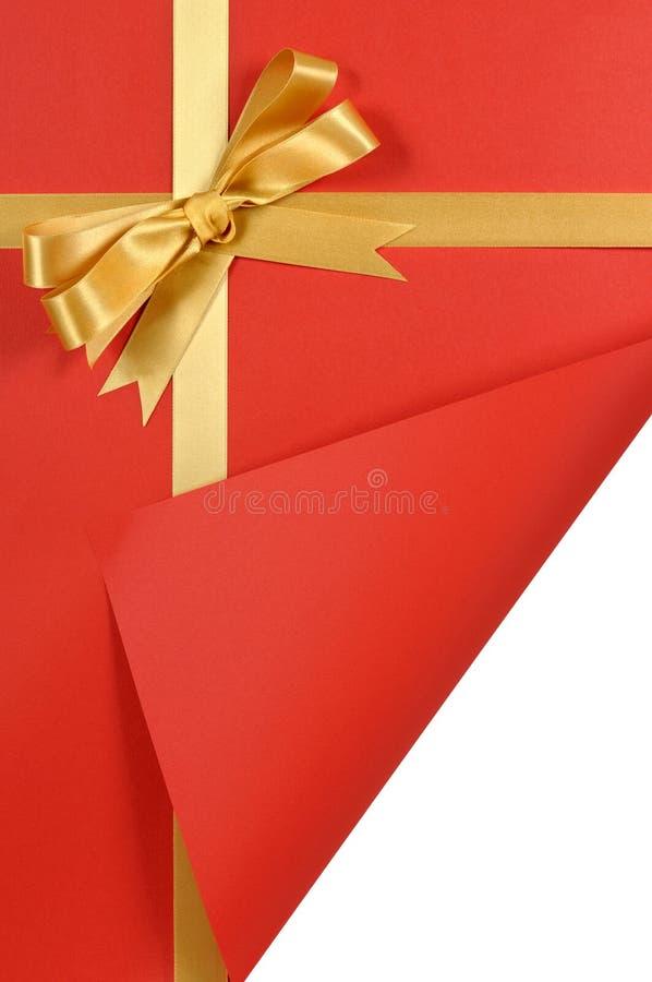 L'exposé introductif de cadeau rouge de Noël, arc de ruban de cadeau d'or, a courbé l'espace blanc de indication de copie de coin photographie stock