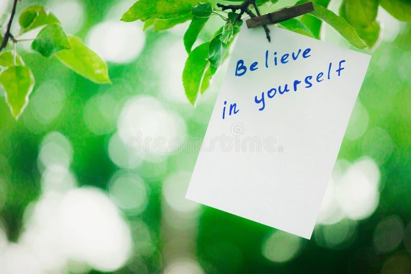 L'expression de motivation croient en vous-même Sur un fond vert sur une branche est un livre blanc avec une expression de motiva images libres de droits