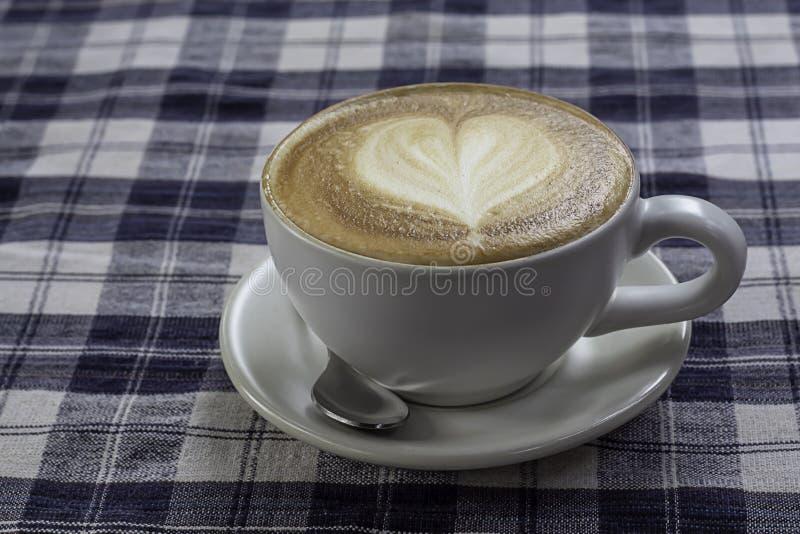 L'expresso chaud de café a complété avec du lait en forme de coeur en verre blanc sur la table avec le chintz Scott photographie stock