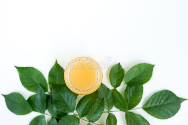 L'extrait naturel dans le conteneur en verre, essentiel organique de nouveau rose sur le fond blanc avec l'espace de copie photos stock