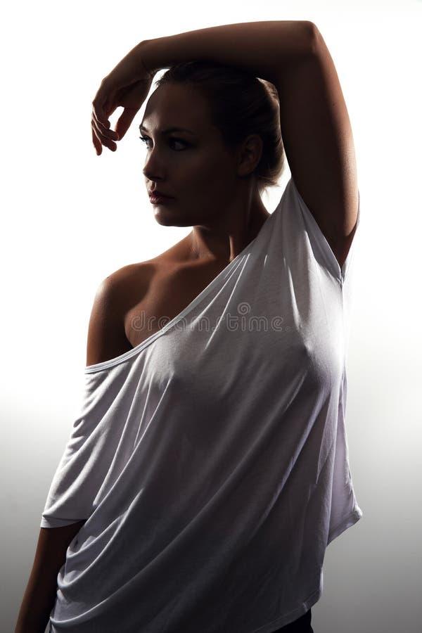 L?g-tangent studiost?ende av den ursnygga kvinnan med blont h?r och den vita t-skjortan arkivfoton