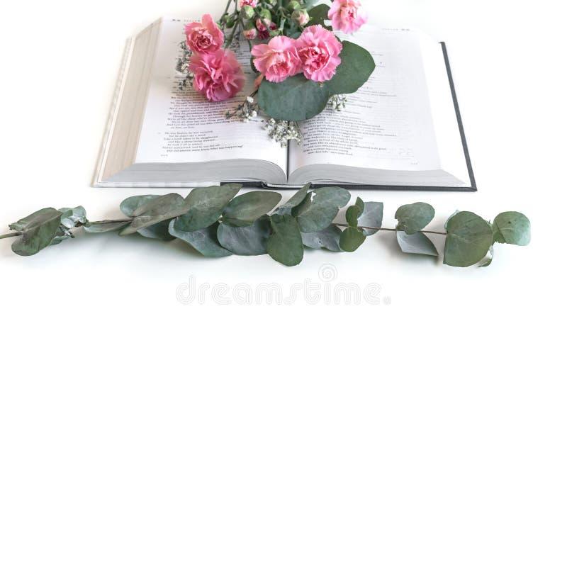 L?genheten l?gger: Bibel och rosa, r?d rosa blommabukett P? vitbakgrund arkivbild