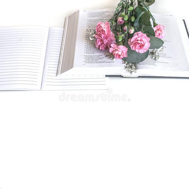 L?genheten l?gger: Bibel och rosa, r?d rosa blommabukett P? vitbakgrund royaltyfri bild