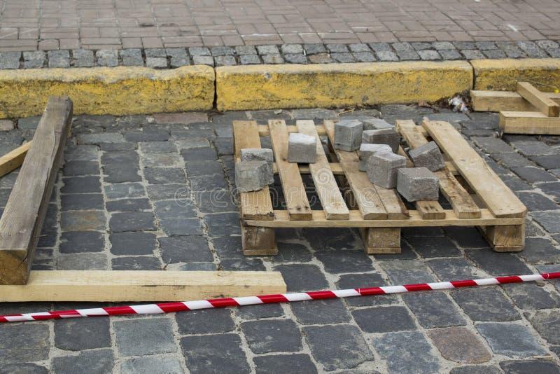 L?gga granitkuber p? en palett p? stenv?gen Rekonstruktion av trottoaren med kullersten arkivfoton