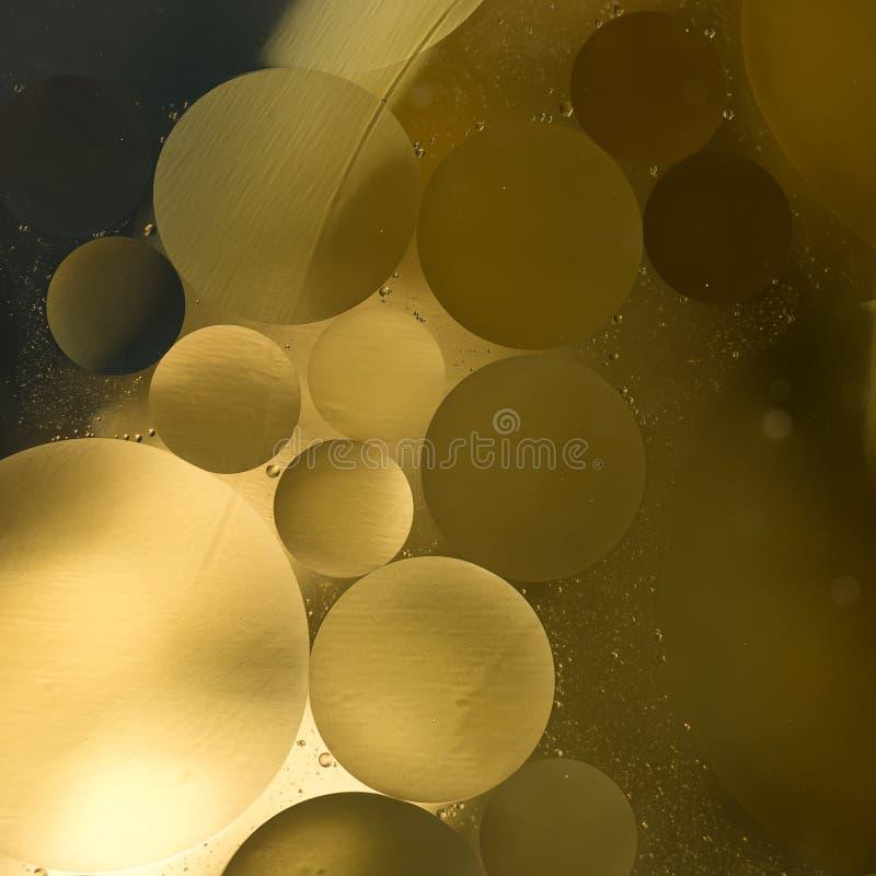 L'or, gradient noir d'huile dans l'eau laisse tomber le fond - résumé image stock