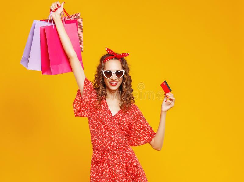 l grappig meisje met plastic creditcard voor het winkelen voor gele kleurenachtergrond royalty-vrije stock foto