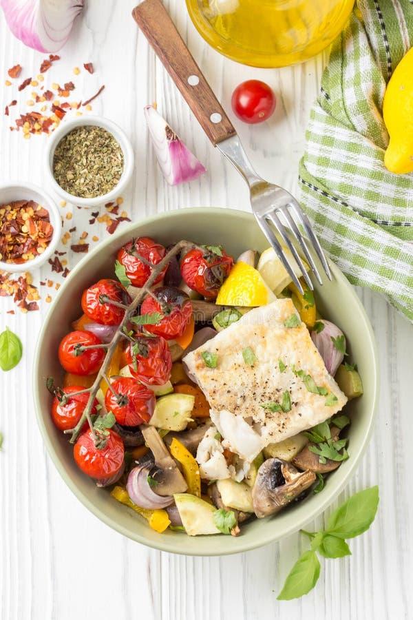 L?gumes cuits au four avec des champignons et des filets de poissons blancs dans la cuvette Courgette, tomates-cerises sur une br image libre de droits