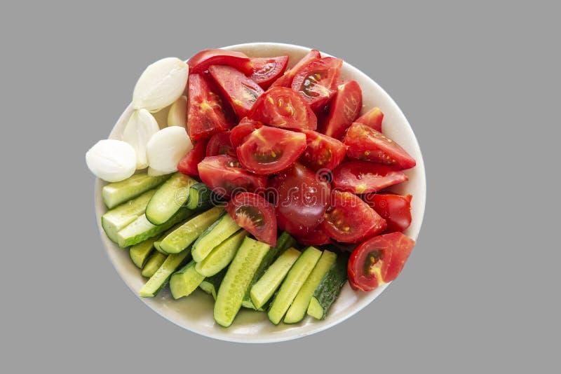 L?gumes d?coup?s en tranches Tomates, concombres et oignons sur un fond gris Chemin de coupure photographie stock libre de droits