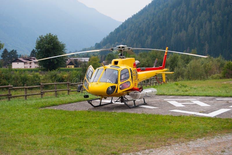 L'hélicoptère alpin jaune de délivrance stationnaire au sol photographie stock
