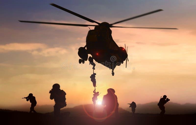 L'hélicoptère d'équipe d'assaut de force spéciale se laisse tomber pendant le coucher du soleil images stock