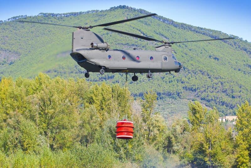 L'hélicoptère de lutte contre l'incendie de l'armée italienne porte un seau en métal complètement de l'eau pour s'éteindre un feu images stock