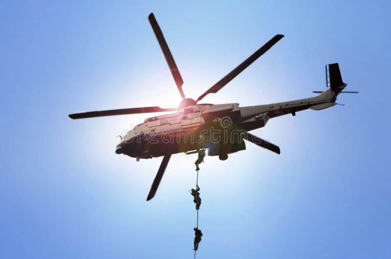 L'hélicoptère militaire de commando se laisse tomber sous la lumière du jour lumineuse images libres de droits