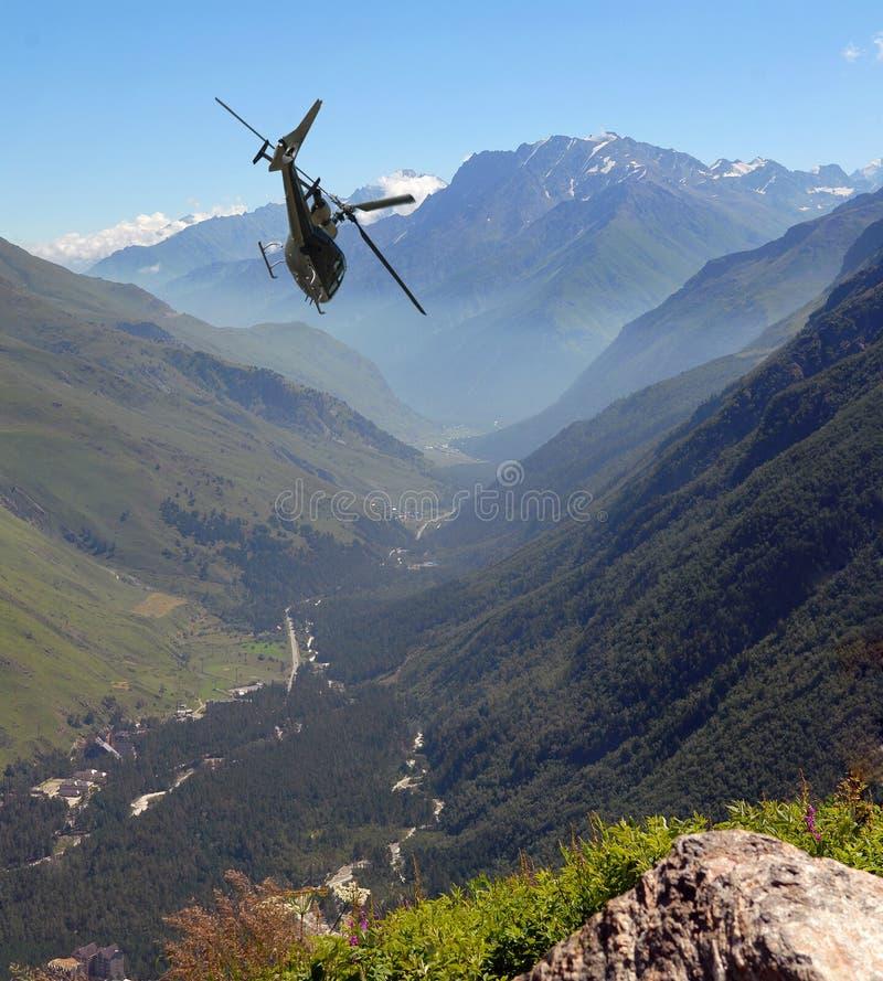 L'hélicoptère vole en montagnes image libre de droits