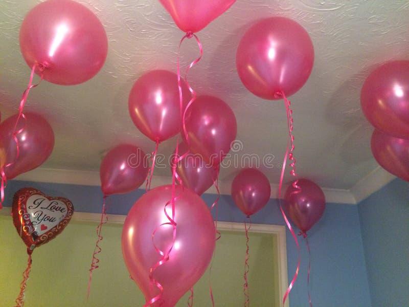 L'hélium rose monte en ballon le flottement dans une chambre avec je t'aime un ballon en forme de coeur dans l'idée très romantiq photographie stock libre de droits
