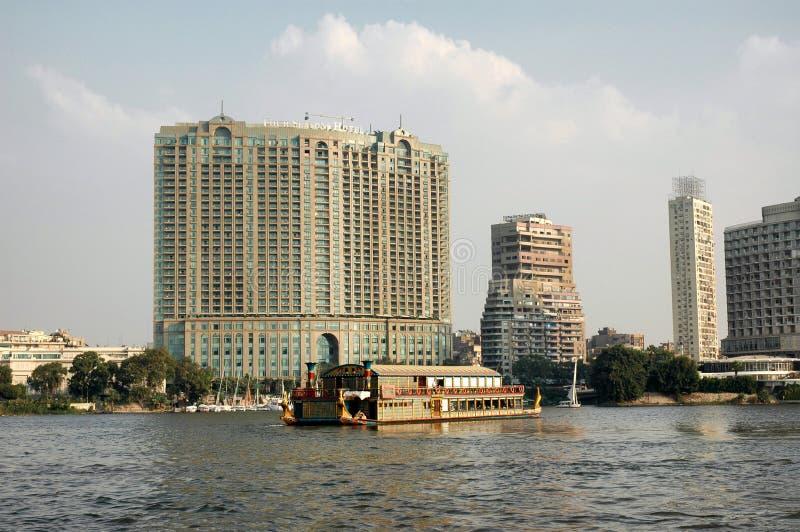 L'hôtel le Caire de Four Seasons vu du Nil avec un bateau de visite passant dans l'avant images stock