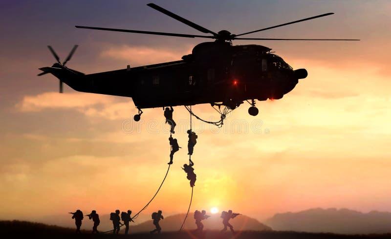 L'h?licopt?re d'?quipe d'assaut de force sp?ciale se laisse tomber pendant le coucher du soleil photo libre de droits