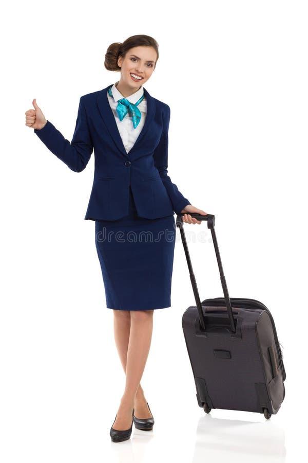 L'hôtesse With Trolley Bag et montre le pouce  image stock