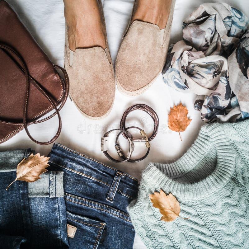 L'habillement d'automne du ` s de femmes a placé - des jeans, des espadrilles de suède, le pull, l'écharpe et le sac en cuir Pied image libre de droits