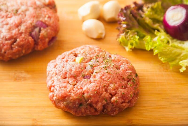 L'hamburger della carne cruda si trova su un bordo fotografia stock