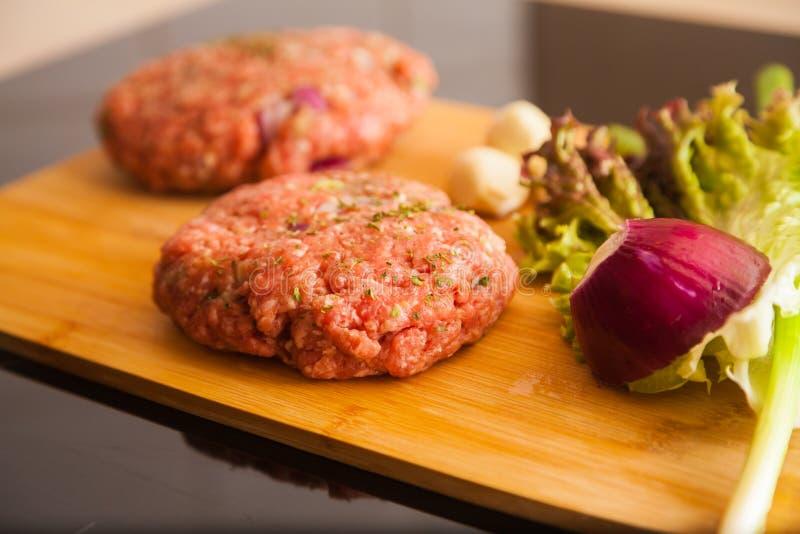 L'hamburger della carne cruda si trova su un bordo fotografia stock libera da diritti