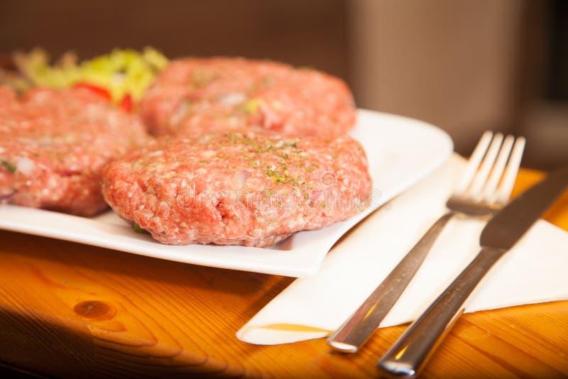 L'hamburger della carne cruda si trova su un bordo fotografie stock libere da diritti