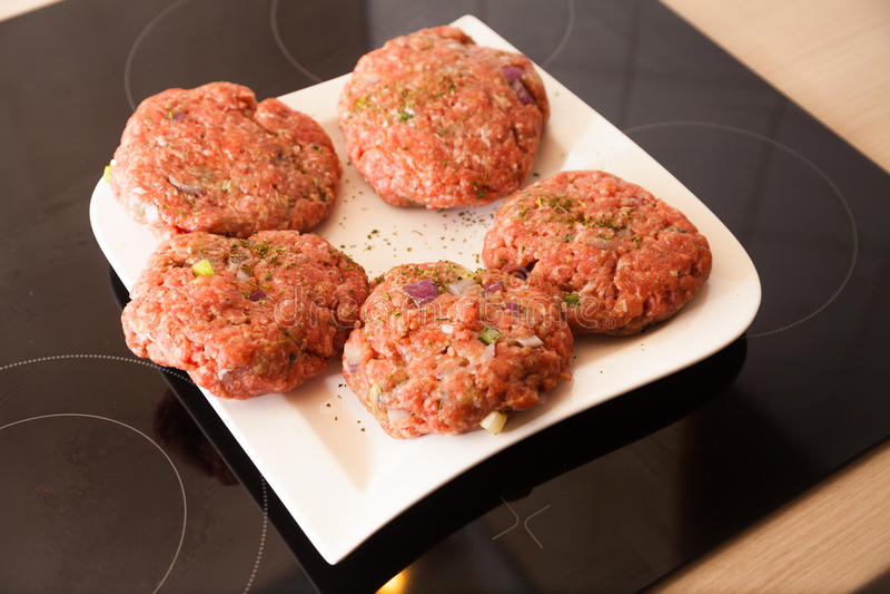 L'hamburger della carne cruda si trova su un piatto fotografia stock