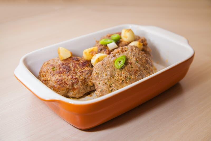 L'hamburger della carne si trova in un piatto di cottura immagini stock libere da diritti