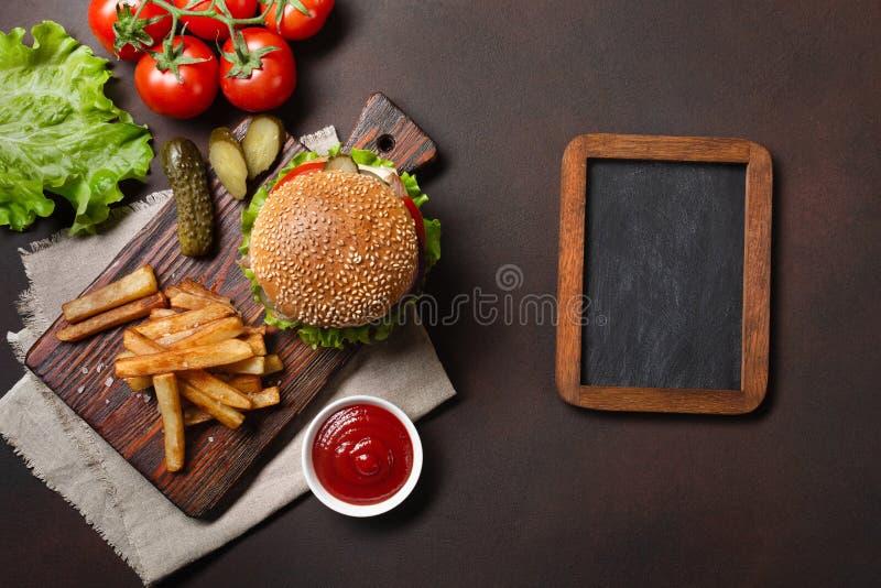 L'hamburger fait maison avec des ingrédients étoffent, les tomates, la laitue, le fromage, l'oignon, les concombres et les pommes photographie stock