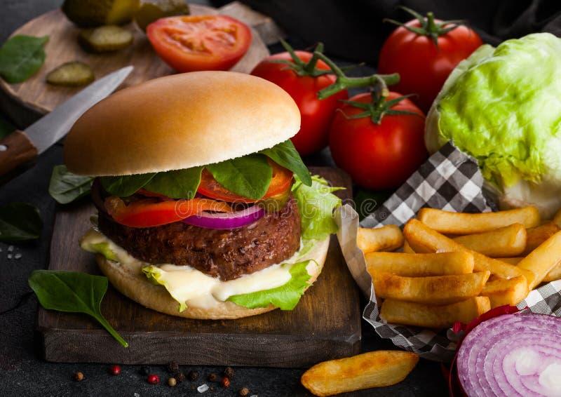 L'hamburger fresco del manzo con salsa e le verdure e le patatine fritte frigge sul fondo di pietra del tavolo da cucina Verdure  immagine stock libera da diritti