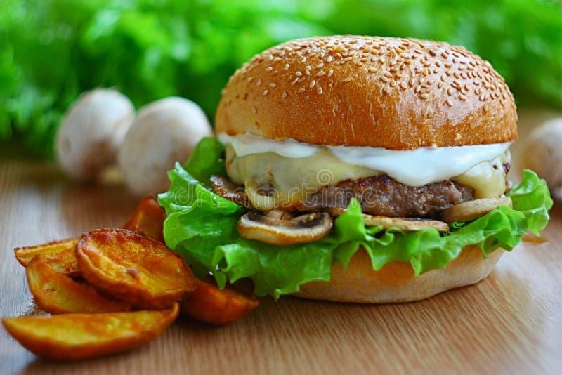 L'hamburger juteux avec du boeuf coupe, fromage, champignons, salade Sur la table parmi les légumes frais et les puces photo stock