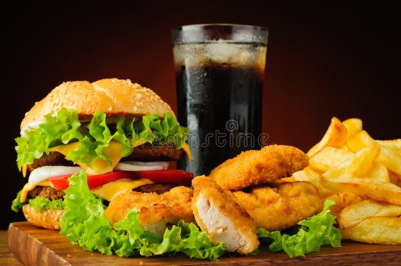 L'hamburger, les pépites de poulet, les pommes frites et le kola boivent images libres de droits