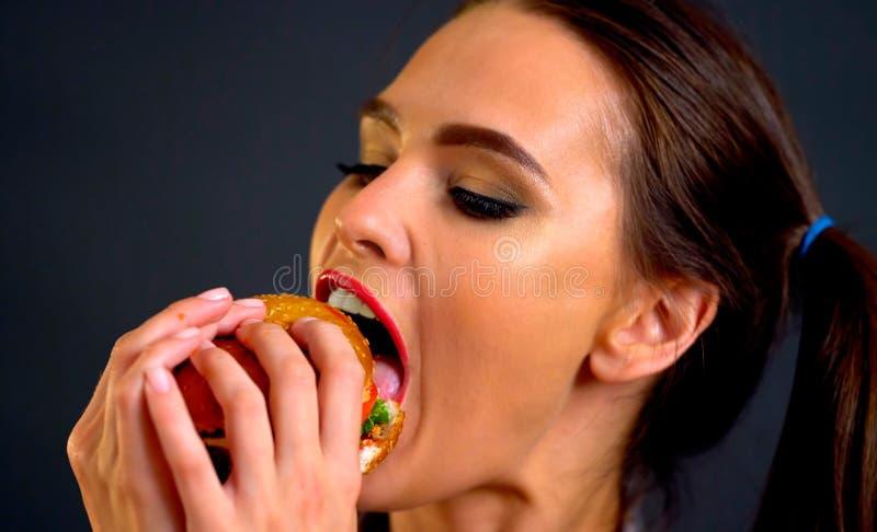 L'hamburger mangeant la femme de concours mangent avec l'appétit photographie stock libre de droits