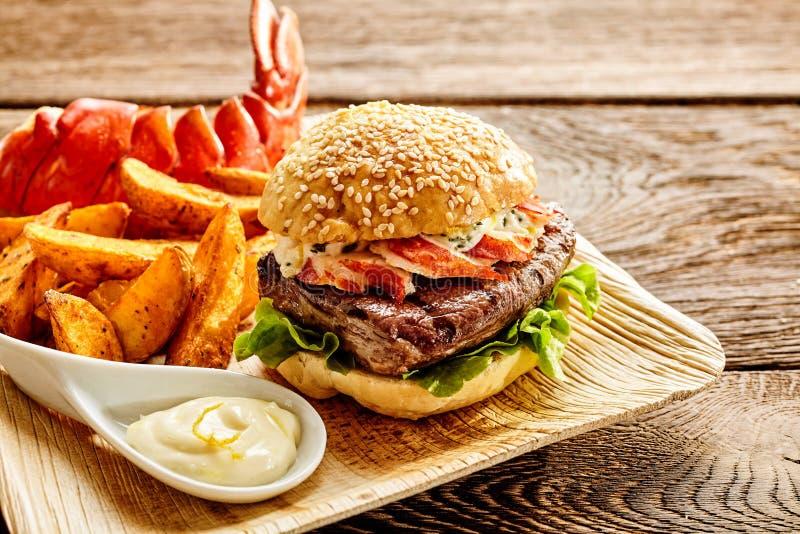 L'hamburger a rempli de lard et de boeuf avec des fritures images libres de droits