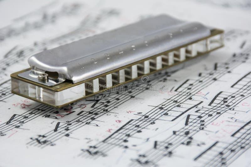 L'harmonica est sur les notes musicales photos stock