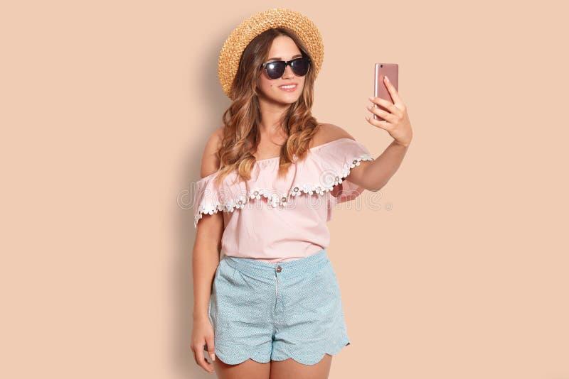 L'heureuse jeune femelle porte les nuances à la mode, chapeau de paille, chemisier et les shorts, fait le selfie au téléphone int photo libre de droits