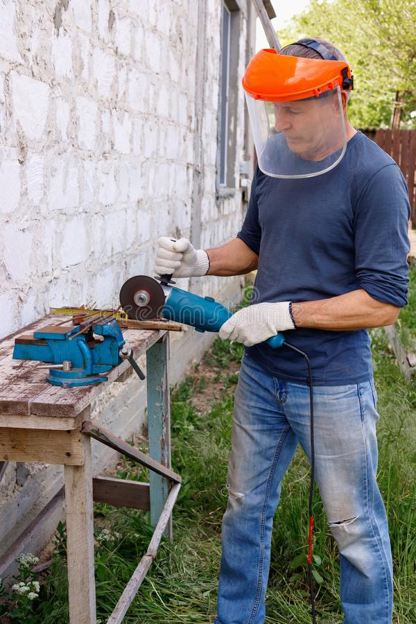 L'heureux travailleur sérieux efficace diligent dépanne avec les outils électriques martèlent et des pinces dans l'arrière-cour d images stock