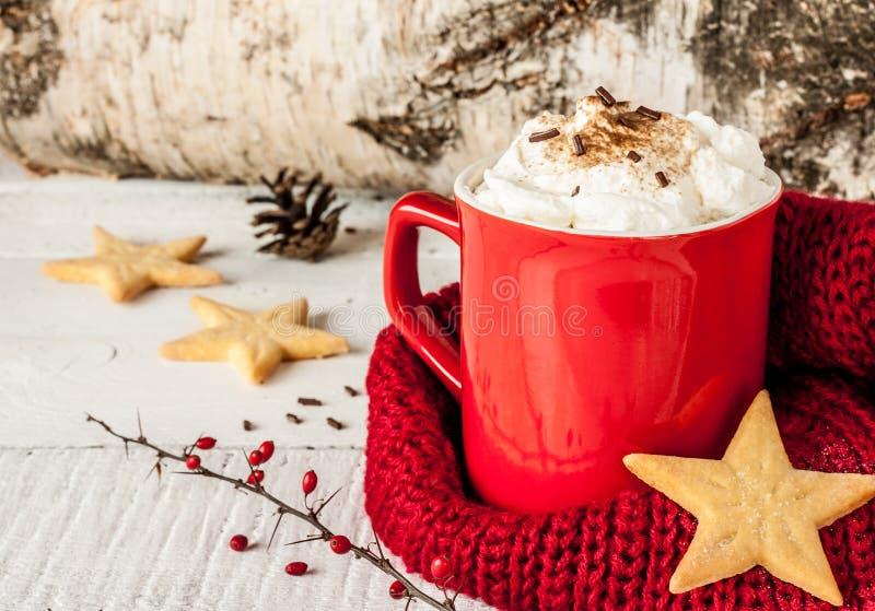 L'hiver a fouetté le café chaud crème dans une tasse rouge avec des biscuits image libre de droits