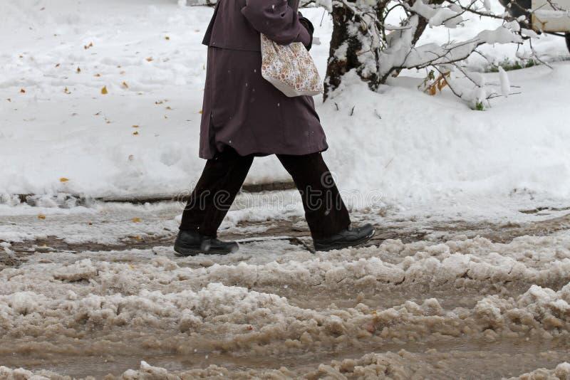 L'hiver Glace neige Les gens marchent dur sur une route glaciale neigeuse passant aux voitures neigeuses sur la rue glaciale non  images stock