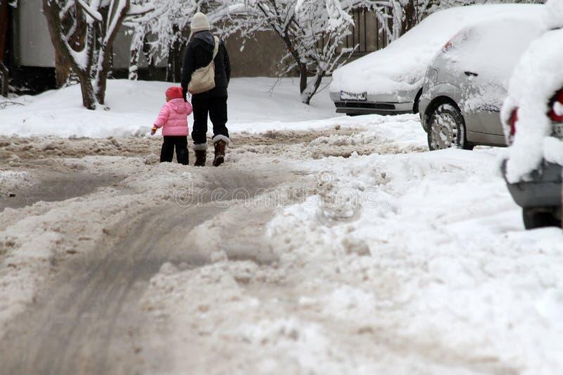 L'hiver Promenade de personnes sur routes très neigeuses Étape de personnes sur une voie neige-égarée Trottoir glacial Glace sur  images stock