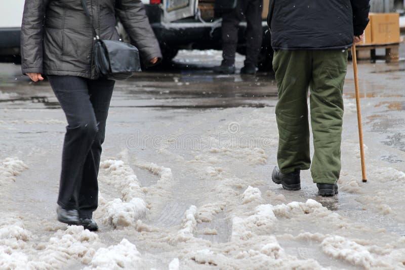 L'hiver Promenade de personnes sur un trottoir très neigeux Étape de personnes sur une voie neige-égarée Trottoir glacial Glace s photographie stock libre de droits