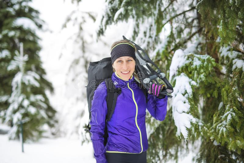 L'hiver snowshoeing Jeune randonneur de femme d'extérieur tenant des raquettes dehors dans la neige photo stock